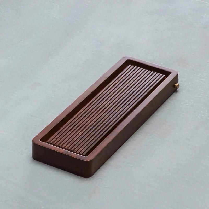 """Dunkelbraune """"Teeplattform"""" (Chatai) aus Holz, die als Arbeitsfläche während der Teezubereitung fungiert."""