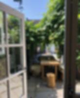 'Tijd voor aandacht' is waar de prachtige kapperszaak Het Haarhuis in Terneuzen voor staat. Zo is ook de tuin volledig ingericht. Een tuin die eenIbiza stijl inademt door de groene schaduw rijke plekken met daaronder eenlange houten tafel, zonnige plekken om te relaxenen heerlijke Rotan hangstoelen om in te zitten.  Toen ik voor het eerst in het Haarhuis kwam, werd ik overdonderd doortwee dingen. De eerste reden was het interieur van de zaak. Prachtig! De vloeren en de muur zijn licht wat ervoor zorgt dat je het gevoel hebt dat je in een luxueuze wereld bent binnen gestapt. Je voelt je gelijk ontspannen.De verlichting in de zaak zorgt ervoor dat er klasse wordt uitgestraald. Daarnaast was eréén ding wat gelijk in het oog sprong. Over de gehele lengte was er in tegenstelling tot het lichteinterieur, een zwarte robuuste toog gehangen. Daarboven hingen de spiegels waar de klanten zichzelf zagen zitten. De belangrijkste plek van de zaak werd hierdoor slim 'uitgelicht'.  Toen ik e