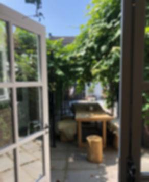 De beste tuinontwerper van Rotterdam,Bedrijfstuin, mooie tuin, rotterdam, tuinontwerper 'Tijd voor aandacht' is waar de prachtige kapperszaak Het Haarhuis in Terneuzen voor staat. Zo is ook de tuin volledig ingericht. Een tuin die de Ibiza stijl inademt door de groene schaduw rijke plekken met daaronder eenlange houten tafel, zonnige plekken om te relaxenen heerlijke Rotan hangstoelen om in te zitten. Tuinontwerp Haarhuis Linda