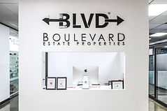 BLVD Estate, inside of their offices. A white wall with BLVD logo and the receptionist desk beneath