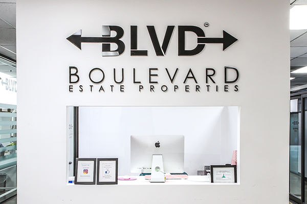 this is an image of the inside look of BLVD estate with a white wall and black BLVD logo