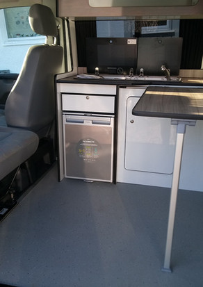 CONVERTED CAMPER INTERIOR WITH TABLE AND ROOM FOR 4 TO EAT