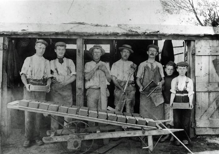 рабочие, формирующие кирпич в ручную