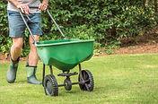 Man seeding and fertilizing residential