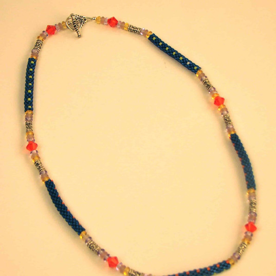 "Mixed glass beads with Swarovski crystal accents, interspersed with ""tube"" beads made from size 11 delicas"