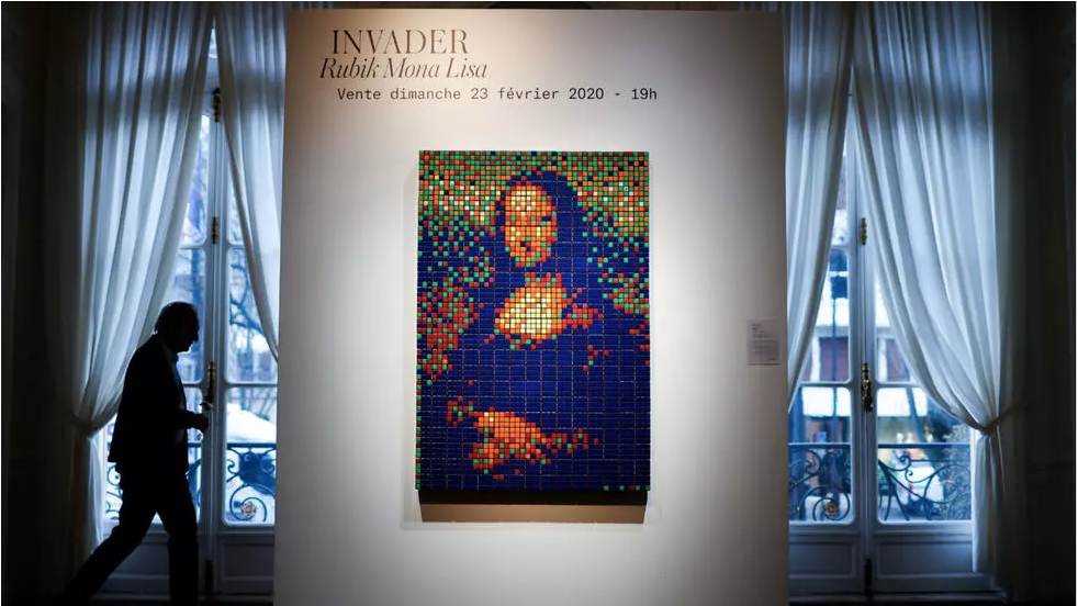 A man walks by the Rubik Mona Lisa (2005) by French street artist Invader displayed at ArtCurial in Paris, France, on February 3, 2020. © Gonzalo Fuentes, REUTERS