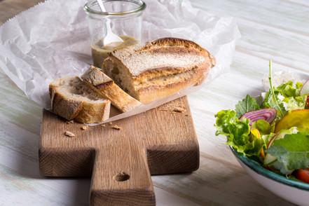 Rustikaler Brotlaib und Brotschneidebret
