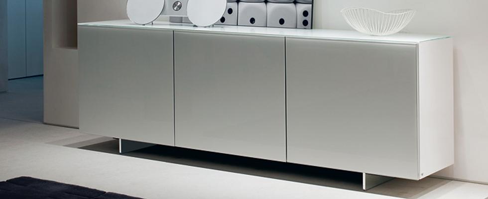 Eleganz in Perfektion. FUTURAvon CATTELAN, designed by Emanuele Zenere, lässt sich mit Glas, Aluminium und Holzelementen kombinieren. Dieses besonders formschöne Kastenmöbel ist mit Glastüren in Aluminiumrahmen, mattverspiegelt oder lackiert lieferbar. Die Füße sind aus Edelstahl oder matt Weiß, Schwarz oder Graphite lackiert. Die Innenböden sind grundsätzlich aus Klarglas, die Version als Anrichte mit dreiTüren hat im Mittelteil eine Innenschublade.