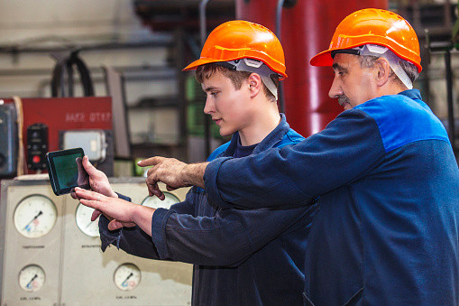 Workers using their mobile device to access safety training on the factory floor with the PinPoint app.
