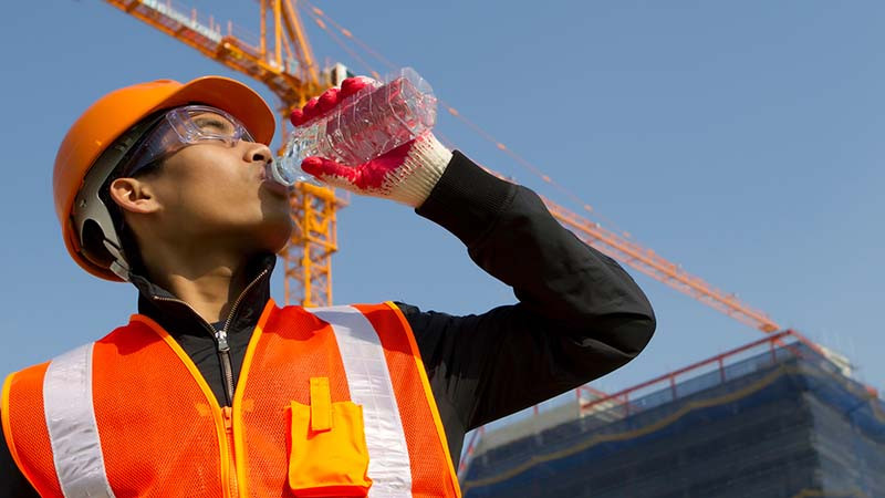 A construction worker drinking water.