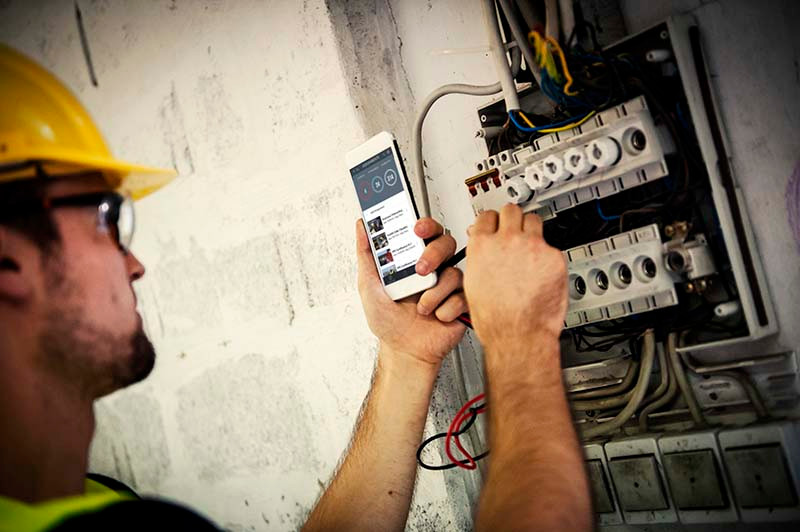 A technician using the error prevention tools in the PinPoint app, on his mobile device, to correct wiring.