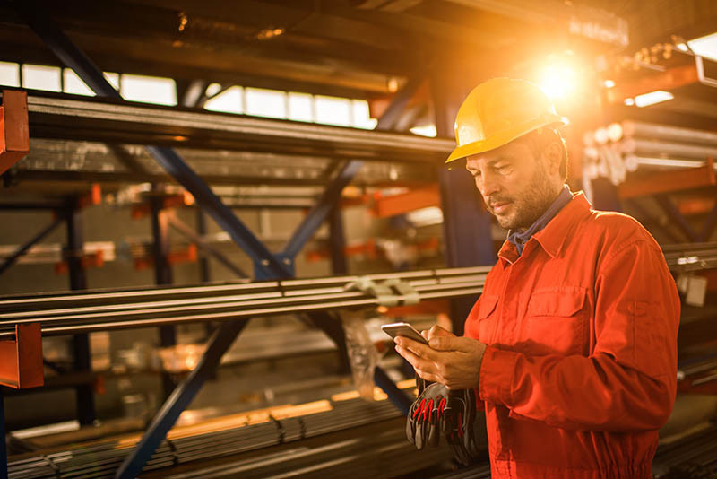 A worker in a warehouse access microlearning on their mobile device with the PinPoint app.