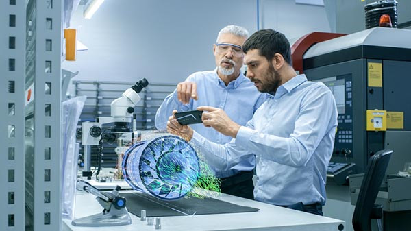 Engineers using augmented reality on their mobile device.