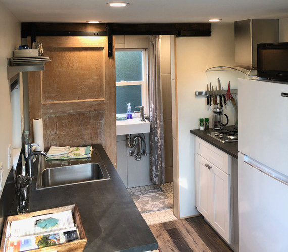 The kitchen and barn door to a full bathroom