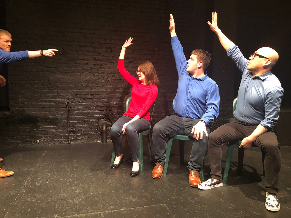 lit comedy performers on stage raising their hands