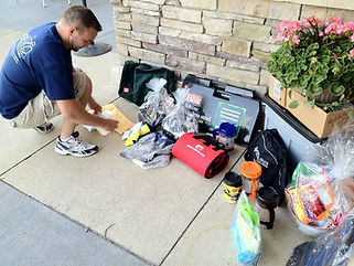 Man kneeling down to contribute items to a donation