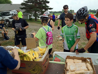 Volunteers handing out food to Bike Sux participants