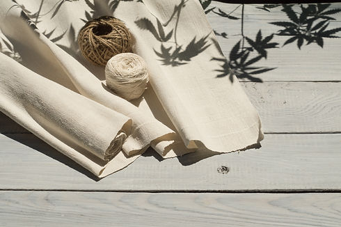Hemp canvas and threads on a white woode