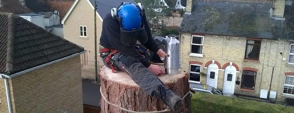 A builder sitting on top of a hight tree stump with their Ghillie Kettle