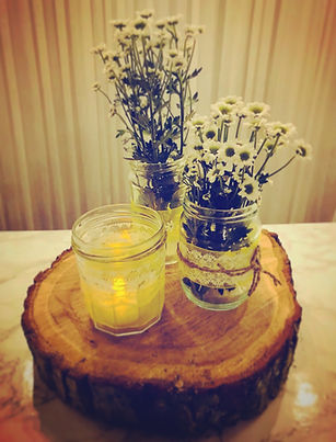 Log and lace centre piece with three decorated vintage jars on a rustic log