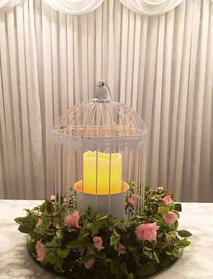 White birdcage centre piece with LE pilla canles & pink rose floral garland
