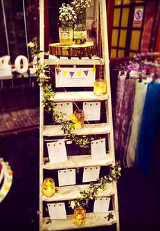 White vintage ladder with table plan finished with vintage jars and flora garlands