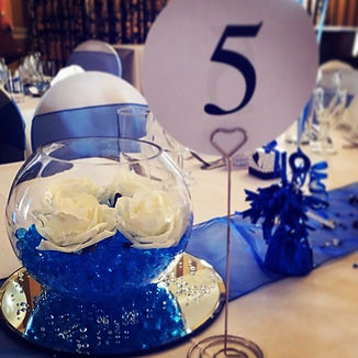 Fish bowl centre piece featuring ivory roses, water beads, scatter crystals and a mirror plate