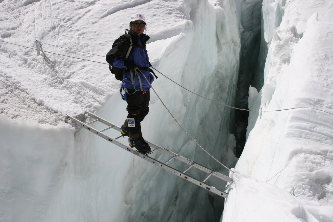 Moni crossing ladder at icefall
