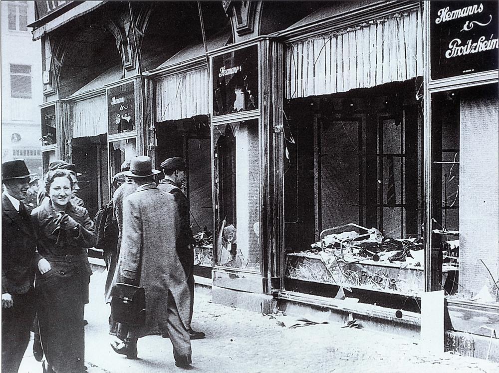 المشاة يعبرون قرب النوافذ المحطمة لمتجر يملكه يهودي في برلين بعد هجمات كريستال ناخت ، نوفمبر 1938