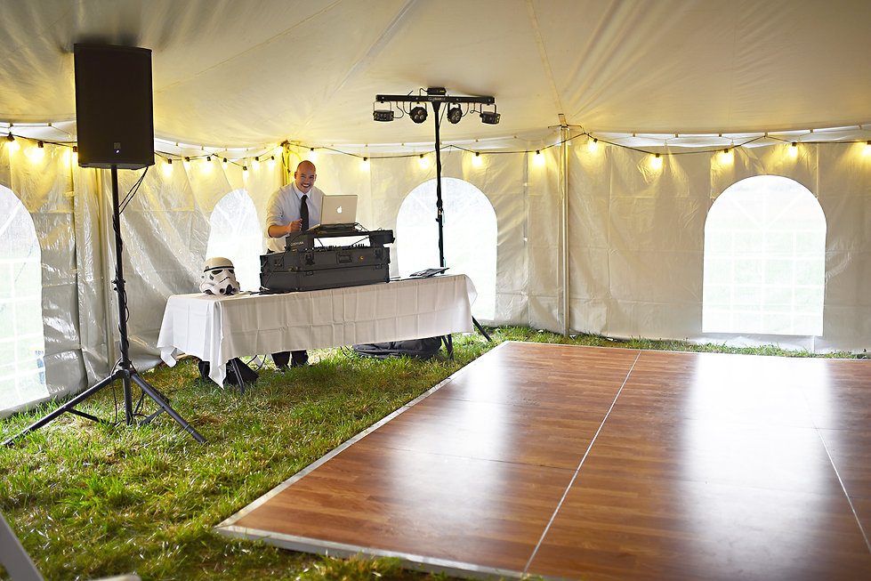 DJ playing music for a wedding reception under a tent