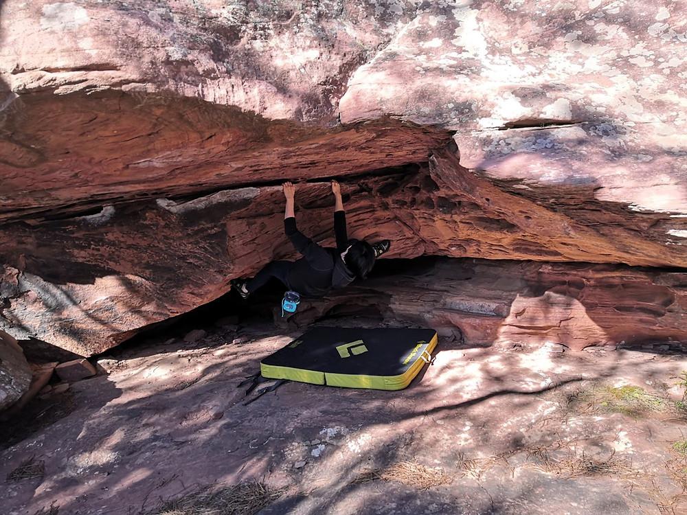 Female climber climbing an overhung boulder in Albarracin, Spain