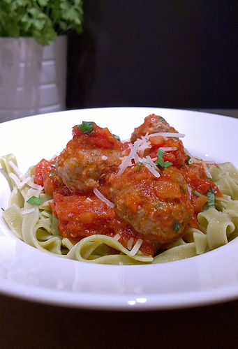 Meat Balls garnished with parmesan and basil.