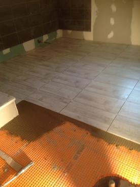 Pose de carrelage au sol sur sol bois dans une salle de bain à Biblisheim