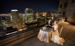 Caucasian groom and Caucasian bride at small table overlooking city