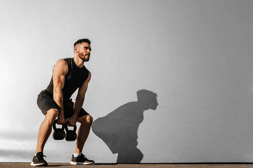 Strong young muscular focused fit man with big muscles holding heavy kettlebells.jpg