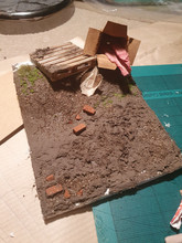 1:25 Scale Artificial Dirt with Pallet and Box. Filler, masonry paint, cork, brick, modelling grass and tufts. balsa wood and kraft card.
