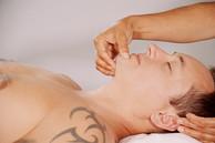 Xiao-Yun Wang pratique un massage chinois du torse et du ventre sur un homme. Elle appuie sur un point du menton.