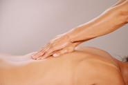 Xiao-Yun Wang pratique un massage chinois général sur une femme. Ses mains glissent le long de son dos.