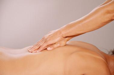 Xiao Yun Wang pratique un massage chinois du dos sur une femme en glissant le long de sa colonne vertébrale avec ses deux mains