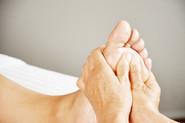 Xiao-Yun Wang pratique un massage chinois des pieds sur une femme. Elle masse sous le pied.