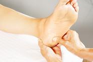 Xiao-Yun Wang pratique un massage chinois des pieds sur une femme. Elle appuie sur un point sous le pied.
