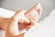 Xiao-Yun Wang pratique un massage chinois des pieds sur une femme. Elle masse la plante du pied avec l'index.