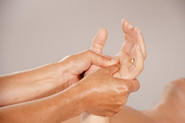 Xiao-Yun Wang pratique un massage chinois du torse et du ventre sur un homme. Elle masse la paume de la main