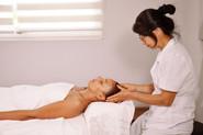 Xiao-Yun Wang pratique un massage chinois général sur une jeune femme. Elle lui masse la tête.
