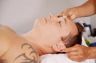 """Xiao Yun Wang pratique un massage chinois du torse et du ventre sur un homme. Elle commence par un point appellé """" troisième oeil""""."""