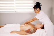 Xiao-Yun Wang pratique un massage chinois général sur un homme. Elle lui masse le ventre.