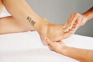 Xiao-Yun Wang pratique un massage chinois des pieds sur une femme. Elle masse les orteils et appuie sur un point de la cheville avec l'autre main.
