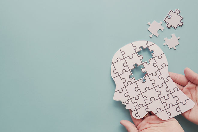 Hands holding brain with puzzle paper cu
