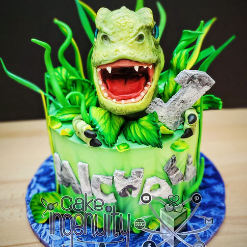 Our popular design of a dinosaur Tyrannosaurus Rex T-rex head popping out of a leafy jungle cake. Perfect for a boys birthday. The head is made of Rice Krispies treats, modeling chocolate, and isomalt eyes. The leaves and name are in fondant. Happy 1st birthday! Baby trex cake