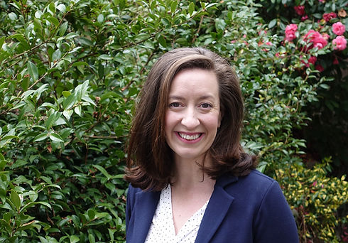 Image of Elena K. Abbott, author of Beacons of Liberty, against blooming camellias
